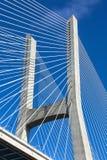 Modern bridge fragment. White cables against bright blue sky Stock Images