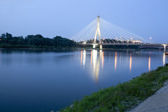 Modern bridge over Vistula River at night. Warsaw,. Night view of a modern bridge over Vistula river, in its pass by the center of Warsaw. Beatiful reflections Stock Photo