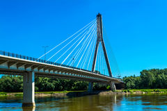 Modern bridge in Warsaw. Sunny summer day with a blue sky and green trees. Royalty Free Stock Image