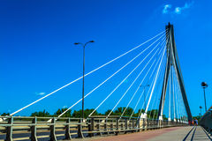 Modern bridge in Warsaw. Sunny summer day with a blue sky and green trees. Stock Photo