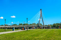 Modern bridge in Warsaw. Sunny summer day with a blue sky and green trees. Royalty Free Stock Photo