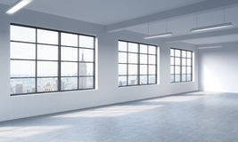 Modern bright clean interior of a loft style open space. Huge windows and white walls. New York panoramic city view. Royalty Free Stock Photos