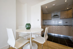 Modern bright kitchen with dining corner. Modern and bright fully fitted kitchen with a dining corner and chairs for four Stock Photos