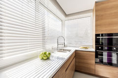 Kitchen with white window blinds. Modern bright kitchen interior with white horizontal window blinds, wooden cabinets with white countertop and household Stock Images