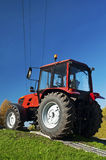Modern bright red tractor outdoors. Modern red tractor on a blue sky background Stock Image