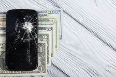 Modern broken mobile phone and money on white wooden background. Copy space. Top view Royalty Free Stock Photography