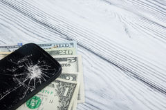 Modern broken mobile phone and money on white wooden background. Copy space. Top view Royalty Free Stock Photos