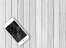 Modern broken mobile phone on white wooden. Background stock photos
