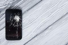 Modern broken mobile phone on white wooden background. Copy space. Top view.  Royalty Free Stock Photos