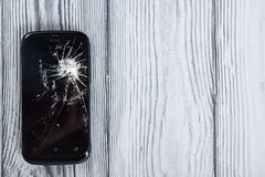 Modern broken mobile phone on white wooden background. Copy space. Top view.  Stock Photo