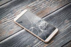 Modern broken mobile phone. Modern broken mobile phone on wooden background stock photo