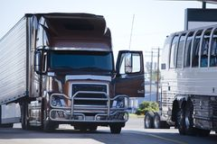 Modern brown big rig semi truck with open door and reefer traile. Modern luxury pearl brown bonnet big rig semi truck with open door and grille guard protector Royalty Free Stock Photography