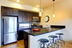 Modern brown kitchen with bar and stools. Stock Photography