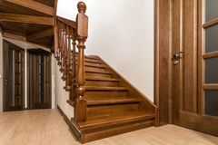 Modern brown oak wooden stairs and doors in new renovated house interior.  royalty free stock images