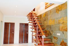 Modern brown wooden stairs. With balustrade in hall Stock Photography
