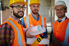 Modern builders. Group of builders in helmets and uniform looking at camera Royalty Free Stock Photo