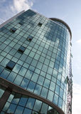 Modern building. Modern corporate building made of glass and concrete. Sky full of clouds is reflected in the green glass royalty free stock photo