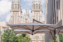 Modern building with a cafe& x27;s big umbrella on a terrace with ancient medieval catholic church facade on a background Stock Images