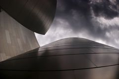 Modern building with cloudy sky. Photo of modern curvy metal building with cloudy sky Stock Photography