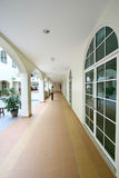 Modern building corridor. Long corridor in a modern church building with arches and glass doors Stock Photo