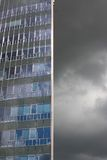 Modern building and dark cloud. Exterior of modern high rise building with glass windows and dark cloudscape Royalty Free Stock Photo
