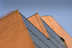 Modern building facade. An abstract angle shot of a brick and glass facade of a building with blank sky above. Brown, earthy and grayish tones Stock Image