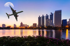 Modern building with flower, airplane and moon in the sky at twi Royalty Free Stock Photography