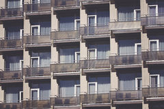 Modern building front wall with repeating pattern of windows and balcony. Stock Photo