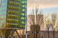 Modern building of glass and The Hague cityscape. Modern glass building skyscraper entrance and The Hague cityscape at the colorful sunset, business area in The Royalty Free Stock Image