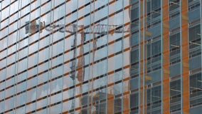 Modern building with glass windows reflected sky and construction crane Stock Image