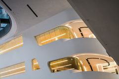 Modern building inside. With slanted and semicircular walls, big windows and balconies, with illumination. Architecture. Geometry. Modern unusual building stock photo