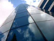 Modern building made of glass reflecting the clouds Stock Images