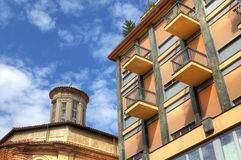 Modern building and old church in Alba, Italy. Fragment of modern building standing near old church in Alba, northern Italy Royalty Free Stock Photo
