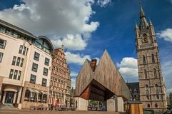 Modern building and old clock tower with clouds and blue sky in Ghent. In addition to intense cultural life, the city is full of Gothic and Flemish style Stock Photography