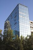Modern Building Santiago de Chile. A modern glass building with a reflex in its glassy windows in Santiago de Chile behind trees royalty free stock images