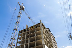 Modern building under construction against blue sky. Tower crane Stock Photo
