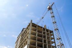 Modern building under construction against blue sky. Tower crane Stock Photo