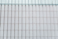 Modern building wall of metal vertical panels and glasses at top Stock Images