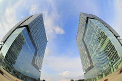 Modern buildings - architectural twins. Fisheye image of two modern tower built face to face Royalty Free Stock Photography