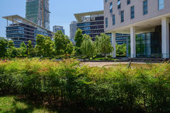 Modern buildings behind hedge in sunny summer Stock Photo