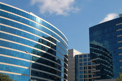 Modern buildings on blue sky background stock images