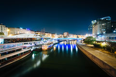 Modern buildings and boats along the Danube Canal at night, in V Stock Image