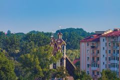 Modern buildings church trees sky. Modern buildings and church among the park trees, blue sky Royalty Free Stock Image