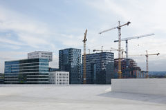 Modern buildings and cranes on duty. A view of some modern buildings and some cranes working on the construction of new ones Royalty Free Stock Images