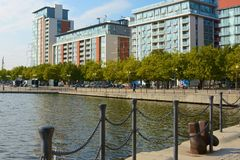 Modern buildings at Docklands in London, England. Docklands in London, England. Modern buildings on waterside with people Stock Image