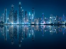 Dubai Marina bay view from Palm Jumeirah, UAE. Modern buildings of Dubai Marina bay with lights at night on background and reflection on water, view from Palm stock photography