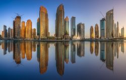 Day view of Dubai Marina bay with clear sky, UAE. Modern buildings of Dubai Marina bay with reflection on water during sunny day, UAE royalty free stock photo