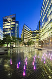 Modern buildings in London at night. Night view of several modern glass buildings near City Hall in London with blue night sky and some fountains stock photography