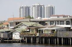 Modern buildings overpower old waterfront homes Bangkok Thailand. Old waterfront homes on the Chao Phraya River Bangkok Thailand Royalty Free Stock Photography