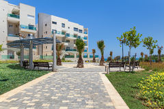 Modern buildings and small square in Ashqelon, Israel. Small city square with palms and benches near complex of modern residential buildings in Ashqelon, Israel Royalty Free Stock Images